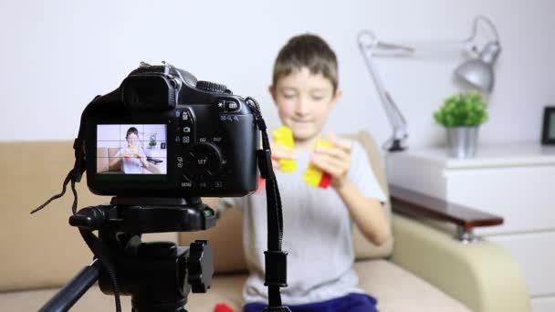 Video von Kamera auf Stativ mit einem jungen auf dem LCD-Bildschirm und verschwommene Szene auf Hintergrund hautnah. Männliches Kind video Blogger Aufnahme Vlog oder Podcast-streaming online