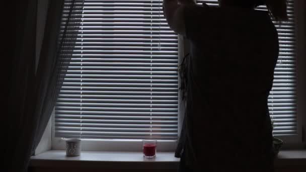Eine Frauen-Silhouette öffnet Jalousien Jalousie morgens zu Hause