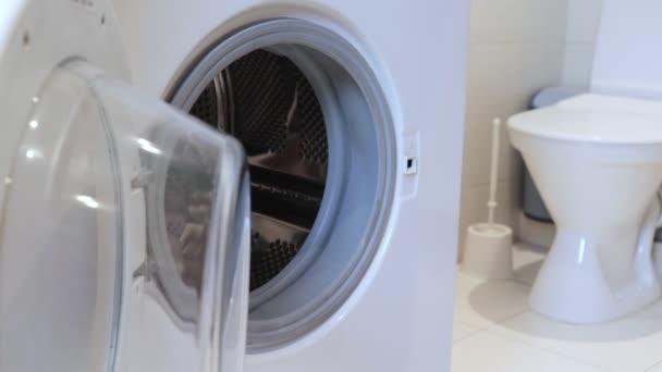 Praní prádla a oblečení koncept, Žena klade špinavé prádlo v pračce a zavře jej