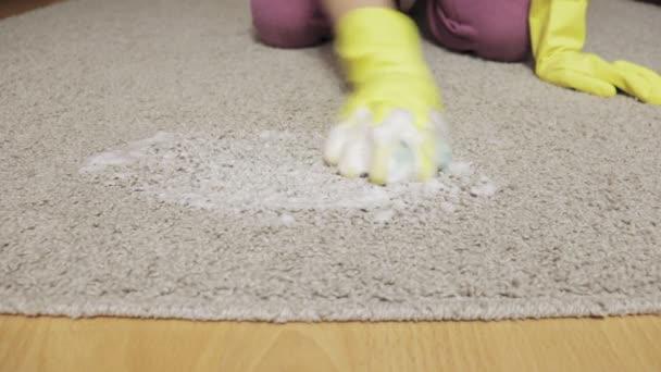 Žena v žluté gumové rukavice čištění koberců s houbou a pěny
