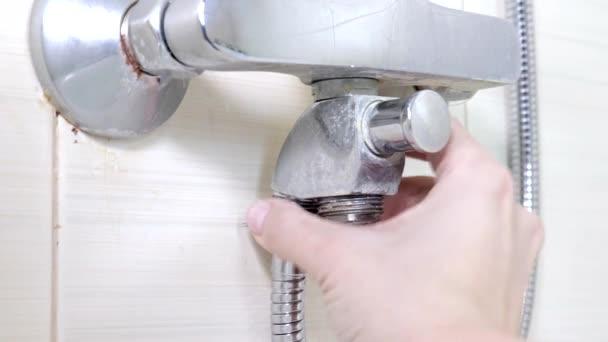 Reparatur des Wasserhahns in der Badewanne, Anziehen der Mutter an einem neuen Schlauch anstelle eines undichten Brauseschlauchs, Reparatur von Sanitäranlagen und Tauchkonzept
