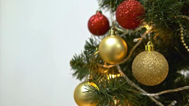 Dekorovaný vánoční stromek s červenými a zlatými prázdninovými míčky, elektrický girland šumivá a blikající zblízka, Nový rok a vánoční tradice na bílém pozadí s kopírovacím prostorem