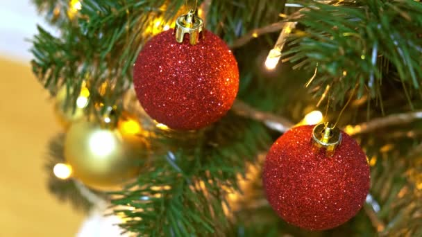 Decorated christmas tree with red and gold holiday balls, an electric garland is sparkling and blinking close up, new year and christmas tradition