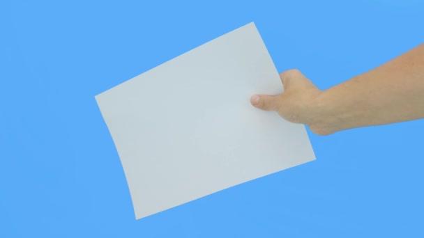 Egy kéz kezében egy fehér üres darab papír A4 másolási hely ellen kék háttér