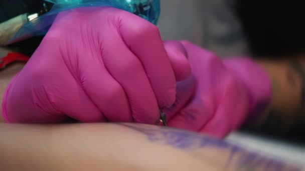 Hands of the artist doing the tattoo for the customer, Tattoo artist in a pink gloves makes a tattoo in a tattoo parlor, close-up
