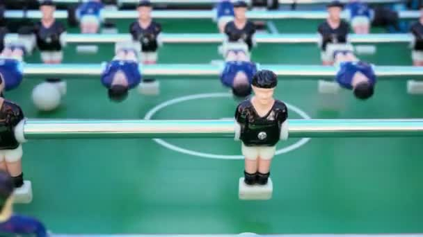 table football, ball game between blue and black on a green football field, close-up on the figures of players