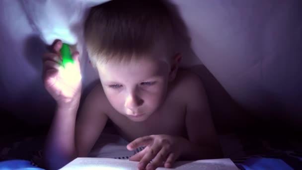 A gyermek olvas egy könyvet egy zseblámpával takaró alatt éjjel. fiú könnyű hajat és kék szemet