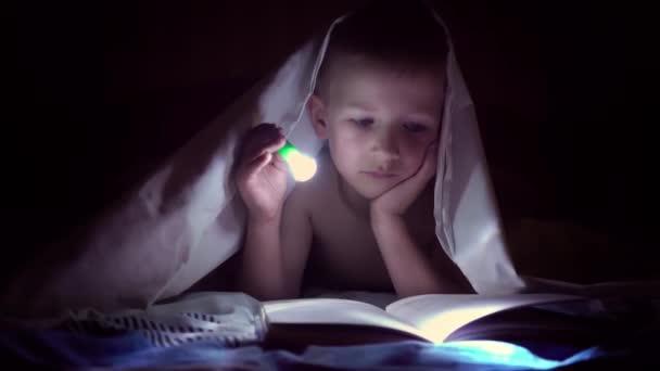 Dítě čte knihu pod deky s baterkou v noci. chlapec s světlé vlasy a modré oči