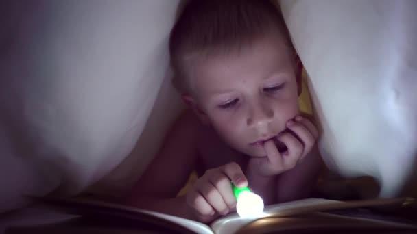 Dítě čte knihu pod deky s baterkou v noci. chlapec s světlé vlasy a modré oči. pohádka před spaním