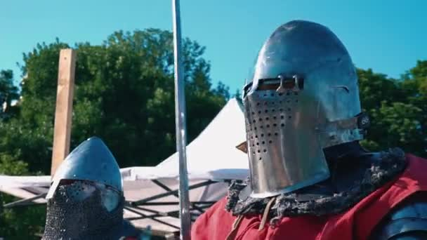 Knight Tournament. Knight before the fight. Man in iron armor with sword in hands against the blue sky