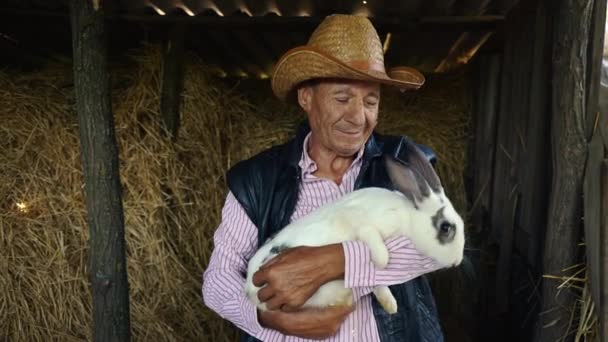 An elderly farmer in a straw hat is holding a large white rabbit. Portrait of a man in the background of hay