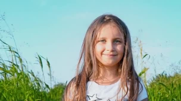Portrait of attractive little girl with a big green eyes on nature background with developing hair