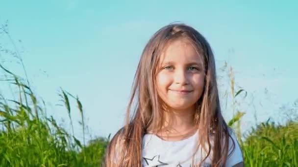 Portrét atraktivní holčička s velkýma očima zelené na pozadí přírody s vývojem vlasy