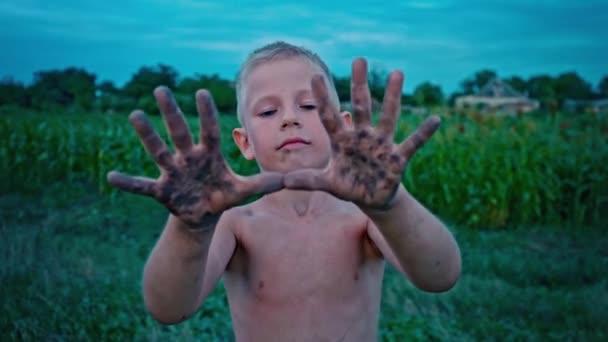 Šťastné dítě ukazuje jeho ruce špinavé od země a smích, chlapec namazal v bahně, veselé dětství zábava