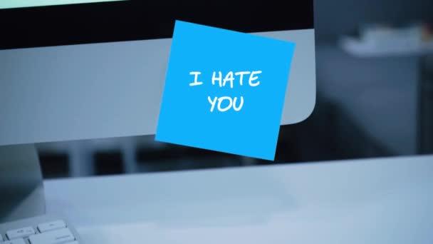 ich hasse dich. die Aufschrift auf dem Aufkleber auf dem Monitor. Botschaft. Motivation. Erinnerung. handschriftlicher Text, der mit einem Filzstift geschrieben wurde. Farbaufkleber. eine Nachricht für einen Mitarbeiter, einen Kollegen