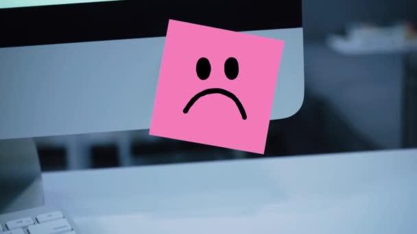 Smutný úsměv. Smutná tvář maloval na štítku na monitoru. Zpráva. Motivace. Připomenutí. Ručně psaný text napsán fixou. Barva štítku. Vzkaz pro zaměstnance, kolegy