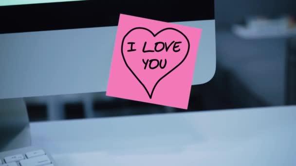 Miluju tě. Nápis na nálepce na monitoru. Zpráva. Motivace. Připomenutí. Ručně psaný text napsán fixou. Barva štítku. Vzkaz pro zaměstnance, kolegy