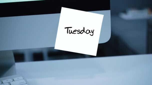 Tuesday. Days of the week. The inscription on the sticker on the monitor. Message. Motivation. Reminder. Handwritten text written with a marker. Color sticker. A message for an employee, a colleague