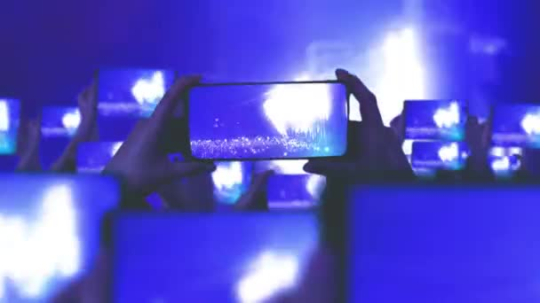 Fans are recording videos on smartphones. A lot of smartphones. Live Stream. Stories. The crowd watches a concert, sings, jumps. Strobing stage lights. Happy people are watching an amazing concert