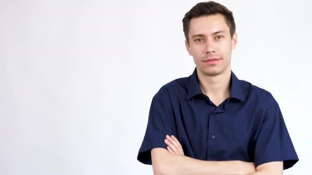 Mladý muž v modré košili na šedém pozadí odkazuje stranou mu