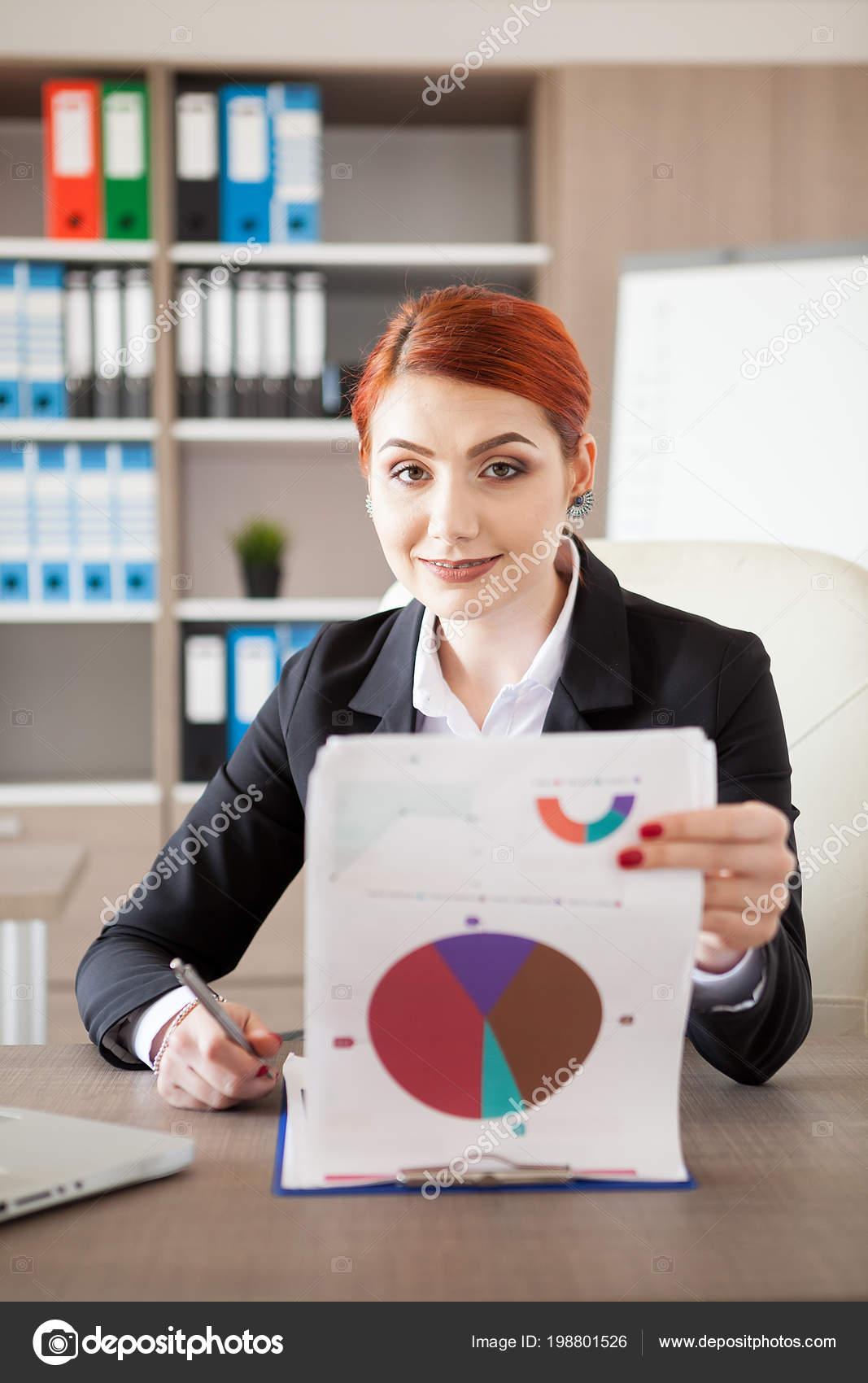 Бізнес-леді в офіційний костюм у себе в офісі дивлячись документи та  pappers з діаграмами на них– стокове зображення 4c6f004bad4b4