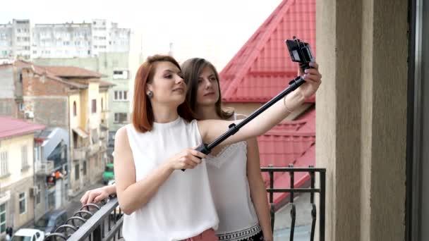Two gogeous women on the balcony taking a selfie