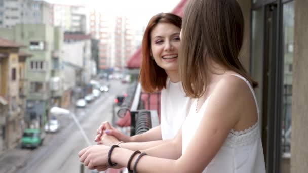 Two women smiling and laughing on balcony