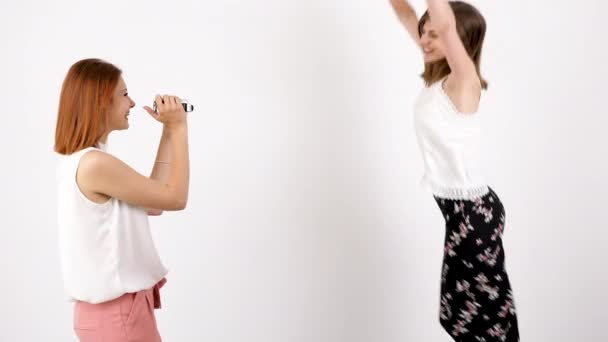 One young woman is filming the other over a white wall