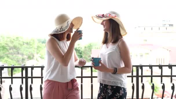 Two gorgeous young women in large summer hats on the balcony drinking coffee and talking