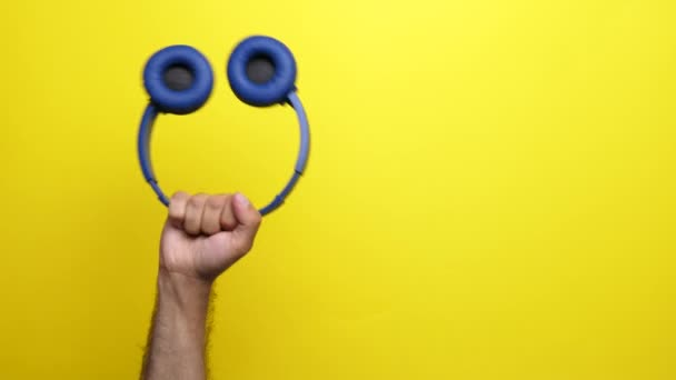 Man hand rising a blue wirelless headphones