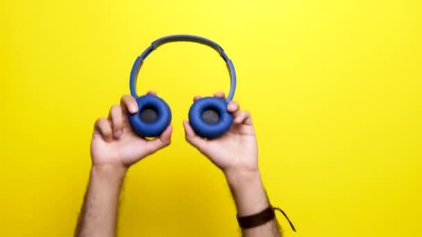 A kezében egy kék fejhallgatók ember kezei