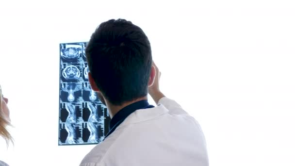Doctor with a woman placing three MRI scan on big white screen