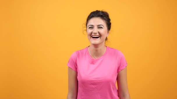 Mladá žena v Růžové tričko usmívá a směje se s přirozené emoce