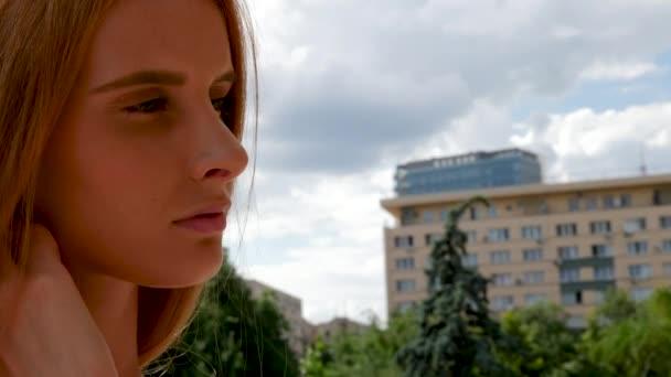 Stylish fashion redhead model posing in the city background