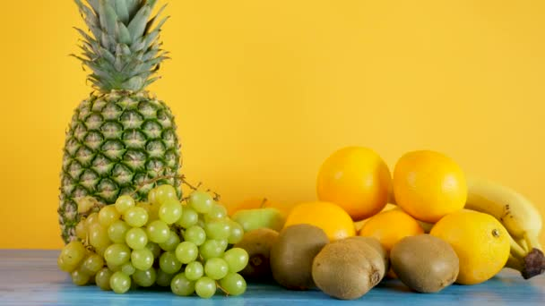 Oranges, bananas, pineapple, kiwi and grapes on yellow background