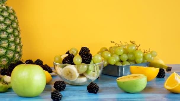 Egészséges és bio gyümölcs saláta készült banán, kivi, szőlő és a bogyós gyümölcsök