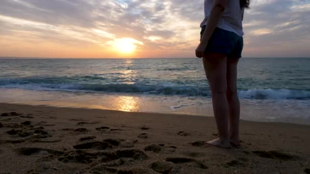 Woman on the beach at the sunrise