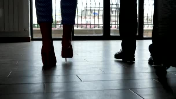 Silhouette of man and woman feet walking toward the office big windows