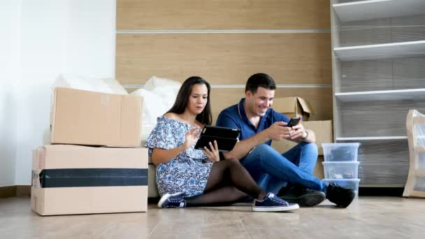 Happy couple in their new flat looking for new furniture online