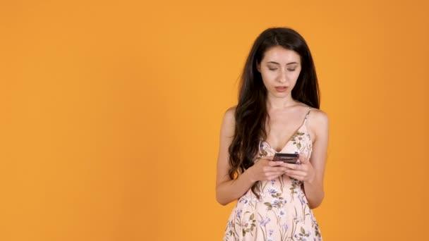 Brünettes Mädchen im Sommerkleid tippt auf Smartphone