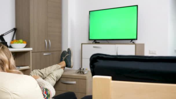 Šťastný pár v jejich útulném bytě sledovat velkoplošnou Tv s zeleným plátnem na něm