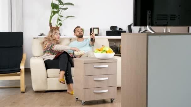 Odhalující záběr páru sledovat televizi v obývacím pokoji