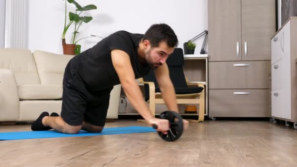 Athletic man doing abs exercises with an ab wheel