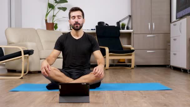 Mann in Lotus Yoga-Pose zu meditieren und mit Blick auf eine digitale Pc