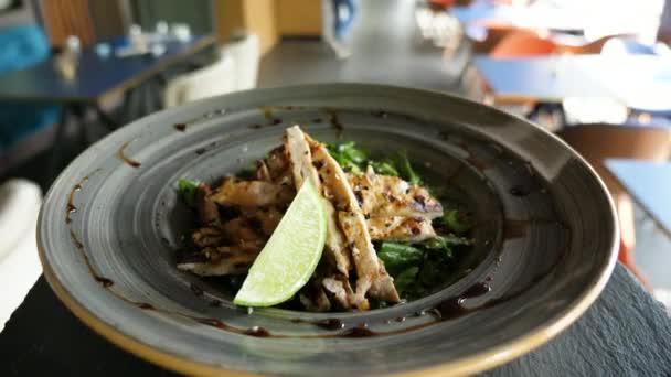 POV záběry desky s avokádovým salátem a grilované kuřecí maso na talíři