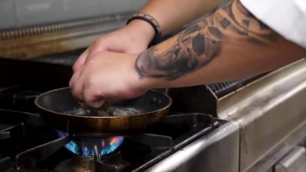 Cook placing foie gras on a pan