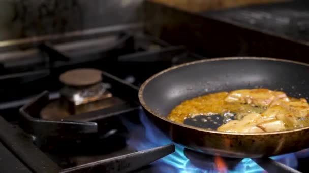 Cook cooking foie gras on stove in kitchen