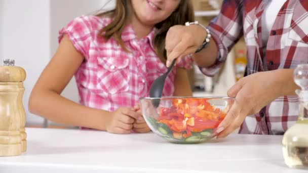 Woman mixing a salad in glass bowl