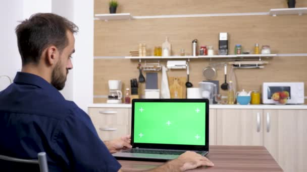 Man at the table in the kitchen looking at laptop
