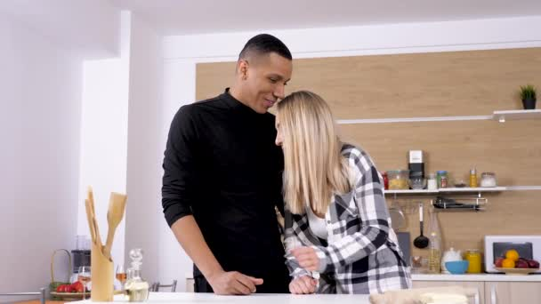 Beautiful young couple at the kitchen embracing each other and laugh